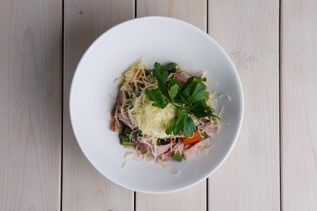 Vista dall'alto di insalata con fagiolini, paprika, prosciutto e formaggio