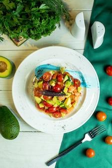 Vista dall'alto di insalata di gamberi con avocado e pomodorini in una ciotola