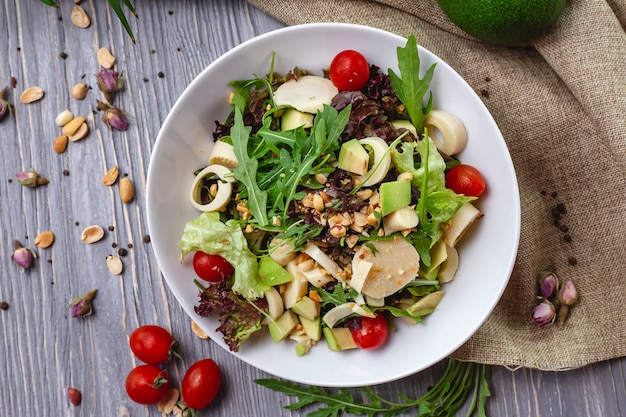 Vista dall'alto di insalata fresca con formaggio pomodorini avocado e arachidi tostate in una ciotola bianca su fondo rustico