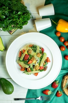 Vista dall'alto di insalata fresca con parmigiano noci pomodori ciliegia e fragole in una ciotola bianca
