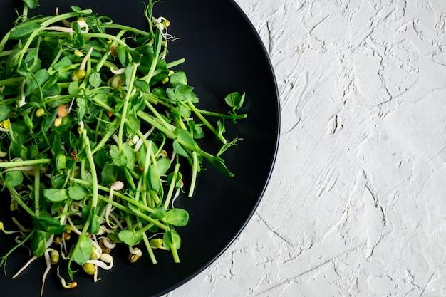 Vista dall'alto di insalata vegana sana fatta di piselli germogli microgreen e fagioli germogliati