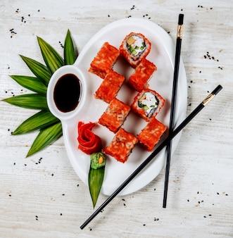 Vista dall'alto di involtini di sushi con cetriolo, bastoncini di granchio, ricoperti di tobiko rosso