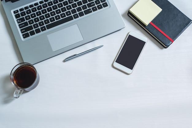 Vista dall'alto di laptop, notebook nero, cellulare, penna, una tazza di tè