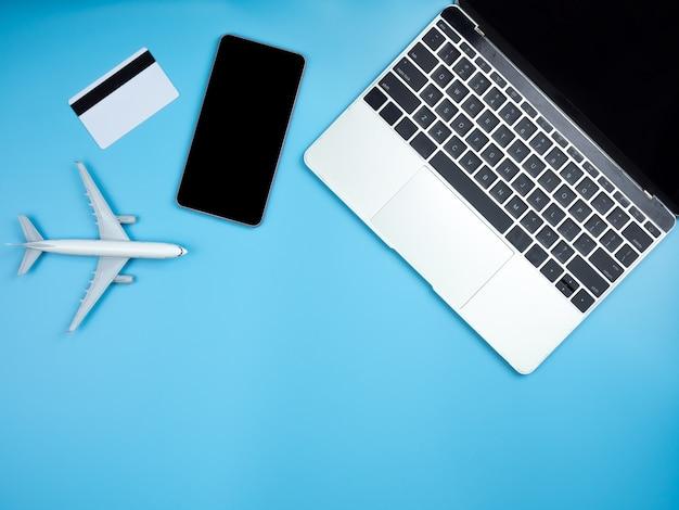 Vista dall'alto di laptop, smartphone, carta di credito e aereo