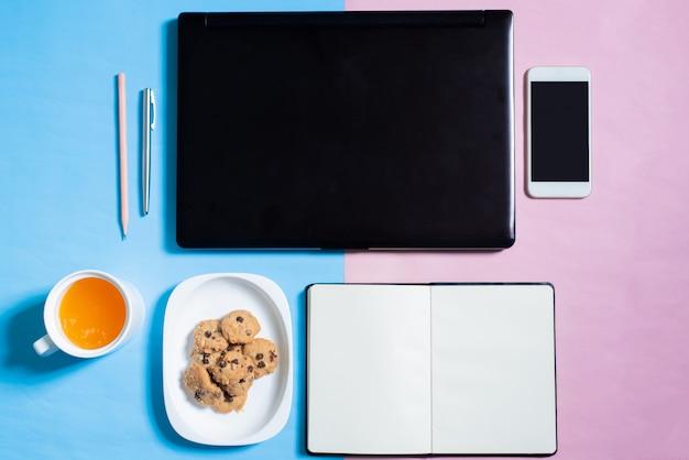 Vista dall'alto di laptop, smartphone, cookie, notebook, penna, matita, succo d'arancia su bakcground blu e rosa di colore pastello