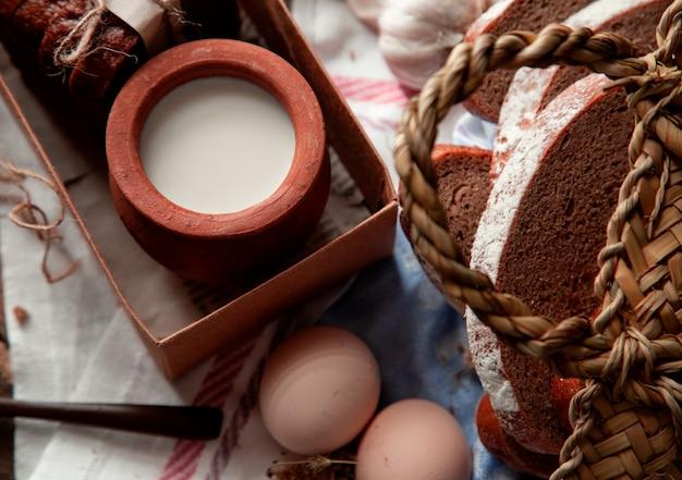Vista dall'alto di latte in una pentola all'interno della scatola, fette di pane e uova.
