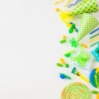 Vista dall'alto di lecca lecca; caramelle; candele; ventilatore del corno di partito; fischio e cappello su sfondo bianco