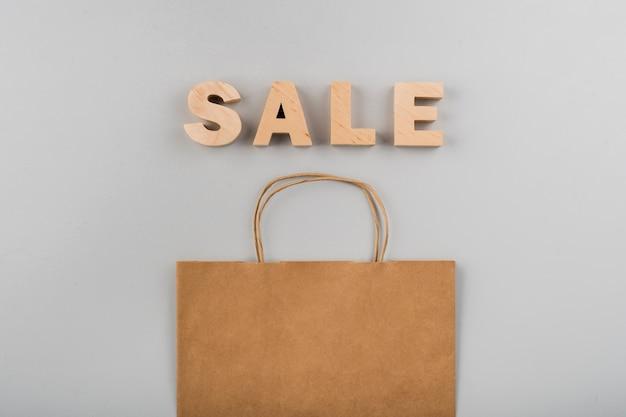 Vista dall'alto di lettere di vendita con un sacco di carta su sfondo chiaro