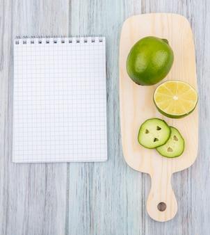 Vista dall'alto di limone fresco con fette sul tagliere di cucina su legno grigio con spazio di copia