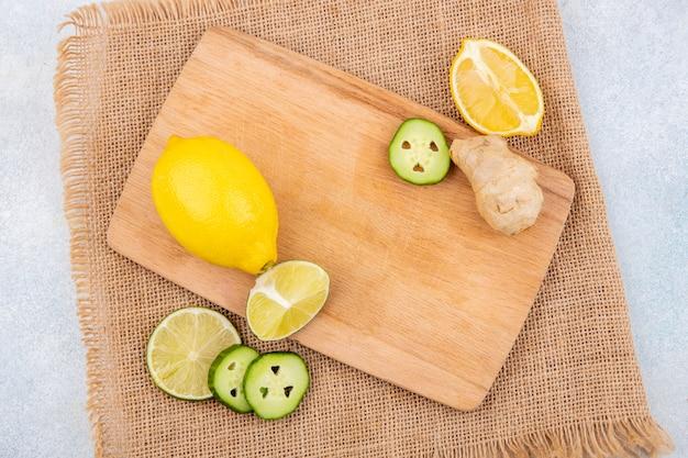 Vista dall'alto di limoni freschi e gialli sulla tavola di cucina in legno con fette di cetriolo allo zenzero sul panno del sacco su bianco con spazio di copia