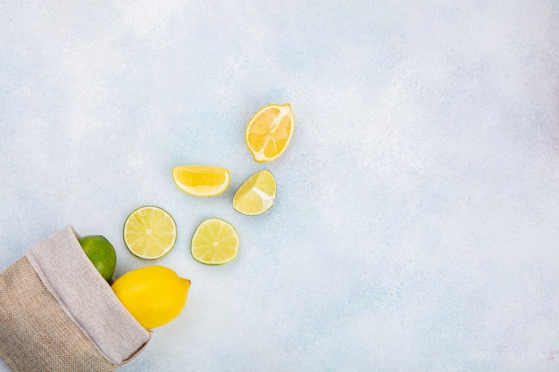 Vista dall'alto di limoni freschi sul sacchetto di tela da imballaggio con fette di limone isolato su bianco con spazio di copia