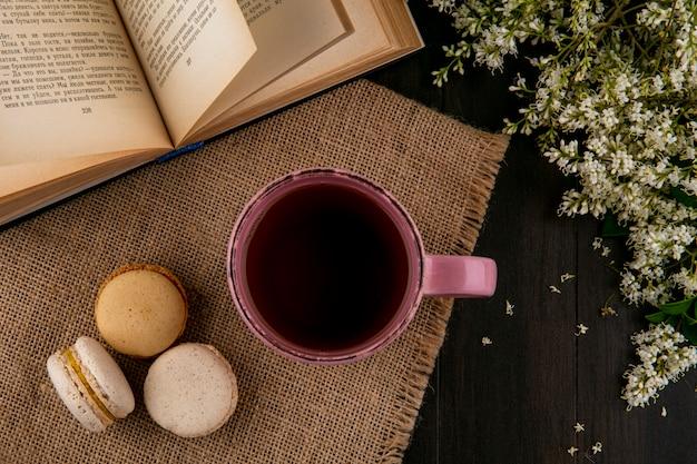 Vista dall'alto di macarons con una tazza di tè su un tovagliolo beige con un libro aperto e fiori