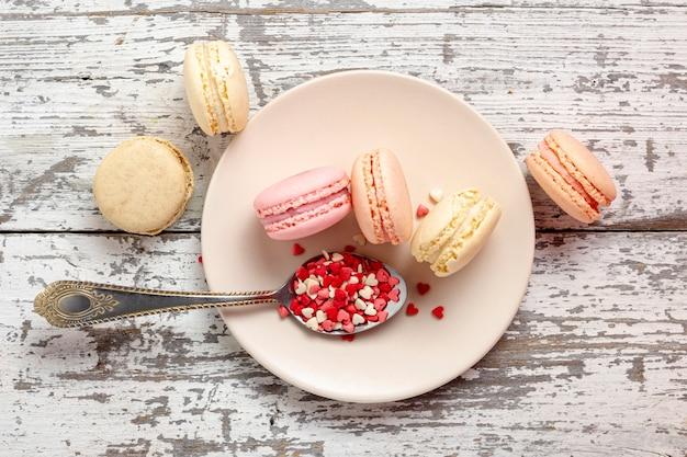 Vista dall'alto di macarons di san valentino sul piatto con cuori