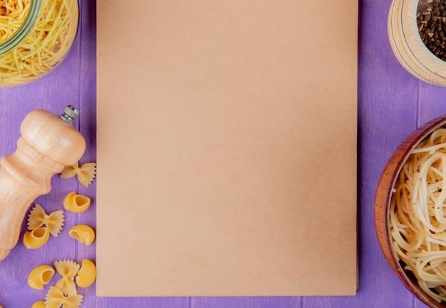 Vista dall'alto di maccheroni come tubi-rigate di farfalle di spaghetti cotti e crudi con pepe nero intorno al blocco note su sfondo viola con spazio di copia