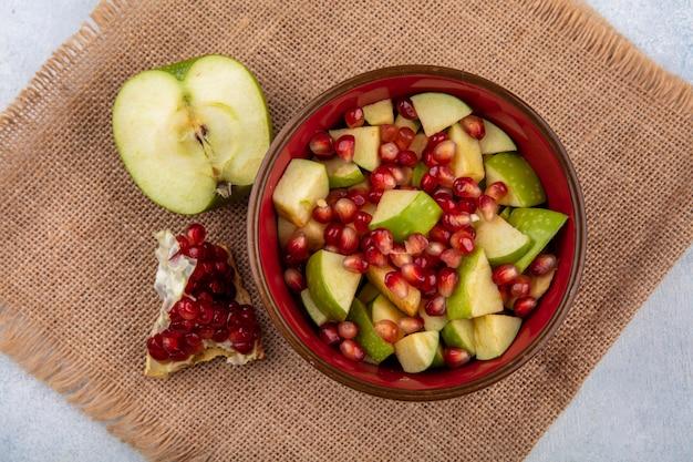 Vista dall'alto di macedonia di frutta con semi di melograno e mele tritate in una ciotola rossa con mezza mela verde e fetta di melograno sulla superficie del panno di sacco