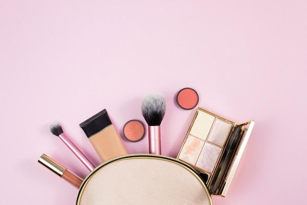 Vista dall'alto di make up prodotti fuoriuscita di una borsa di cosmetici rosa su uno sfondo rosa. concetto di bellezza, moda e shopping