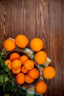 Vista dall'alto di mandarini freschi in un cesto di vimini e arance mature sul tavolo di legno rustico con spazio di copia