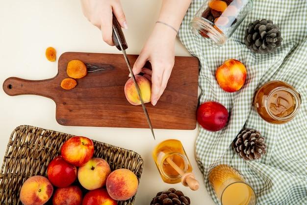 Vista dall'alto di mani di donna taglio pesca con coltello e prugne secche sul tagliere con marmellate e succo di uva passa e pigne intorno sulla superficie bianca