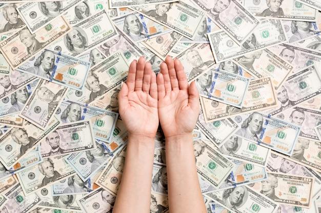 Vista dall'alto di mani femminili su vari sfondo del dollaro. ricchezza con spazio vuoto per il tuo design. accattonaggio concetto di denaro