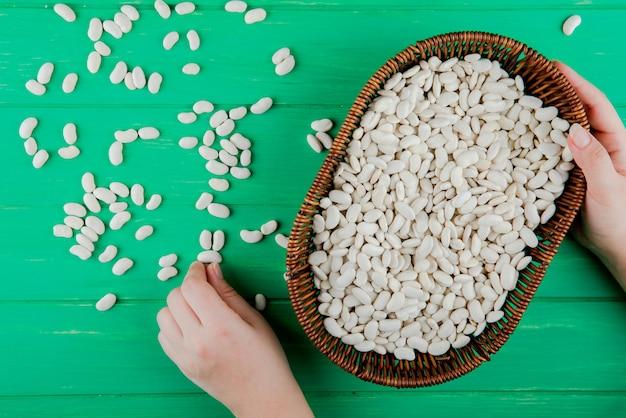 Vista dall'alto di mani in possesso di un cesto di vimini con fagioli bianchi e fagioli sparsi su sfondo verde