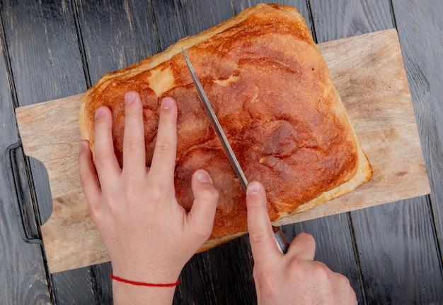 Vista dall'alto di mani maschili, tagliare il pane fatto in casa con un coltello sul tagliere su fondo in legno