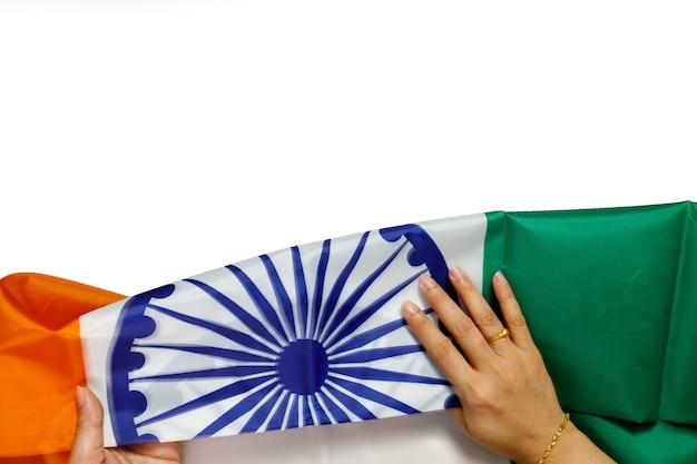 Vista dall'alto di mani umane che tengono una bandiera nazionale dell'india su sfondo bianco.