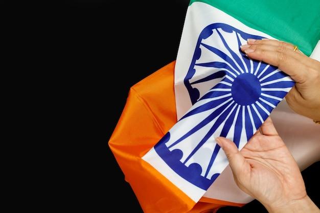 Vista dall'alto di mani umane che tengono una bandiera nazionale dell'india su sfondo nero.