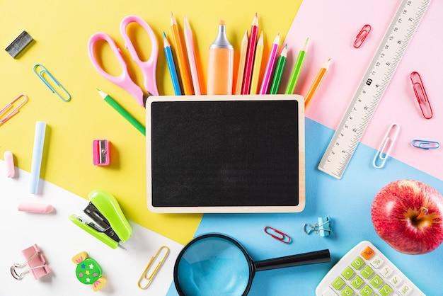 Vista dall'alto di materiale scolastico colorato, stazionario su carta pastello.