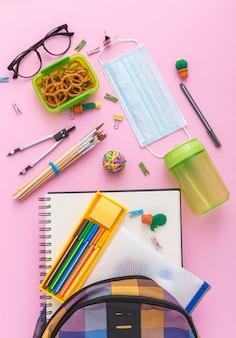 Vista dall'alto di materiale scolastico con borsa libro e matite