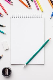 Vista dall'alto di matite colorate con il taccuino