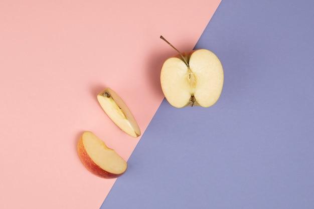 Vista dall'alto di mela su sfondo rosa e viola