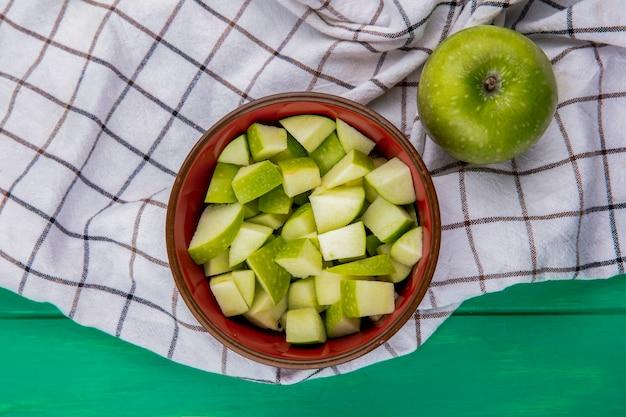 Vista dall'alto di mela verde con fette tritate su una ciotola rossa sulla superficie del panno