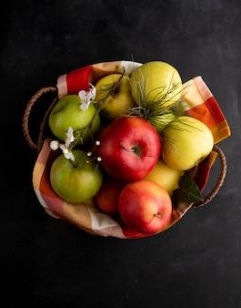 Vista dall'alto di mele colorate in un cestino con un rametto di fiori