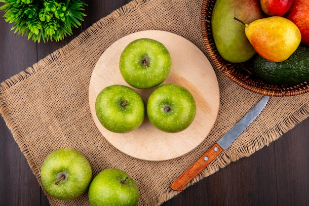 Vista dall'alto di mele verdi su una tavola di cucina in legno con un coltello sul panno di sacco con un secchio di frutti su superficie di legno