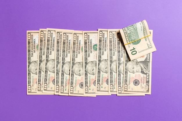 Vista dall'alto di mentire banconote in dollari in una riga su viola