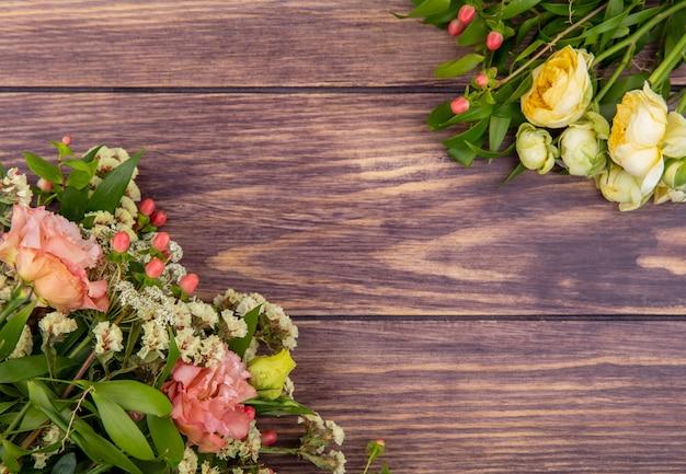 Vista dall'alto di meravigliosi e freschi fiori come peonie e rose su una superficie di legno