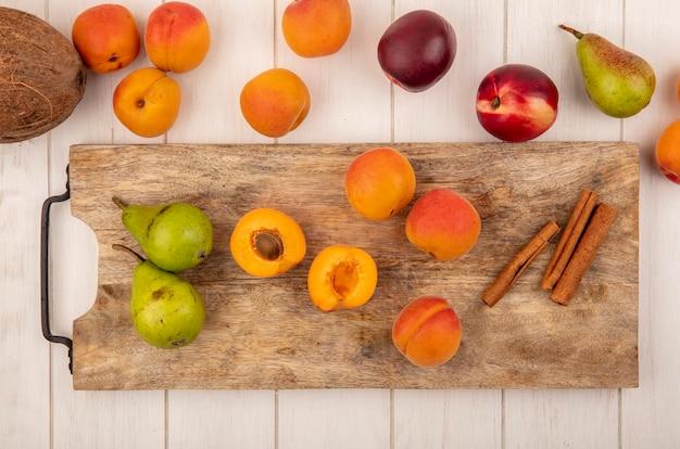 Vista dall'alto di metà tagliata e frutti interi come albicocca e pera con cannella sul tagliere e modello di frutta come pesca pera e cocco albicocca su sfondo di legno