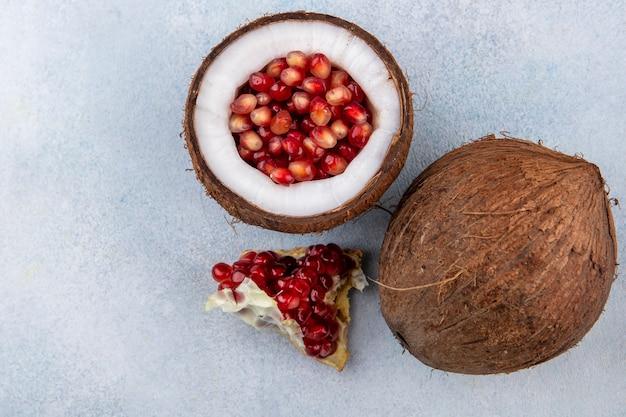 Vista dall'alto di mezza noce di cocco all'interno di semi di melograno con cocco e fetta di melograno sulla superficie bianca