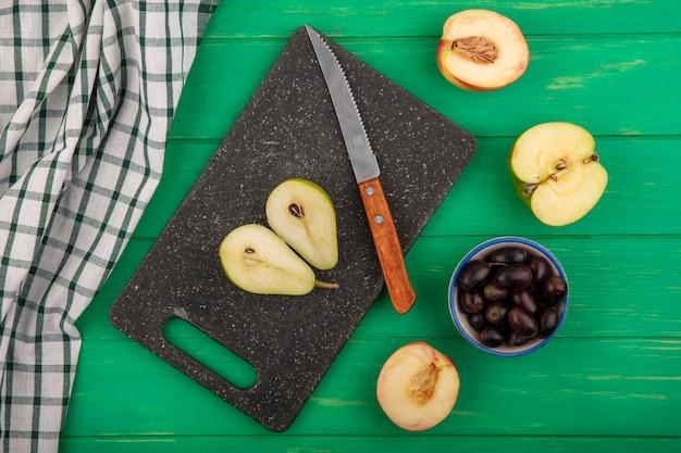 Vista dall'alto di mezza pera tagliata e coltello sul tagliere con panno plaid e metà tagliata pesca e mela metà con acini d'uva su sfondo verde