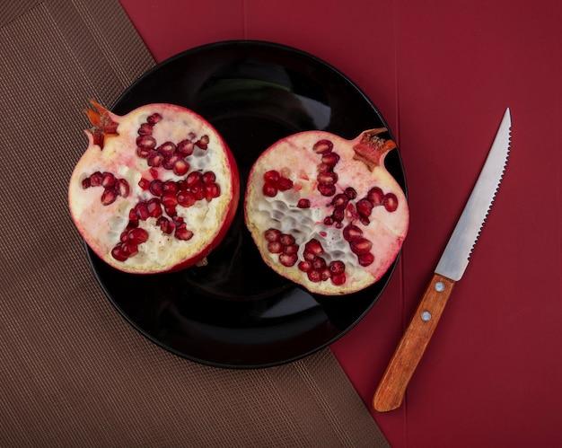 Vista dall'alto di mezzo taglio melograno nel piatto sul panno con un coltello sulla superficie rossa