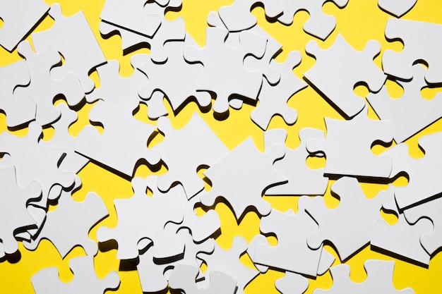 Vista dall'alto di molti pezzi di puzzle bianco