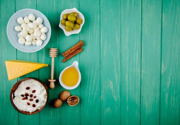 Vista dall'alto di mozzarella in una ciotola di ricotta e un pezzo di formaggio olandese con noci bastoncini di cannella miele e olive in salamoia su legno verde con spazio di copia