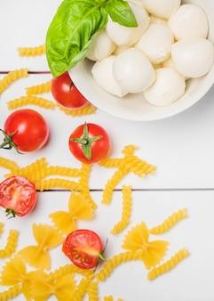 Vista dall'alto di mozzarella italiana con foglia di basilico; pomodori e fusilli