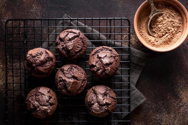 Vista dall'alto di muffin al cioccolato su rack di raffreddamento con cacao in polvere