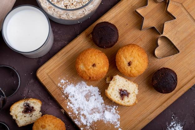 Vista dall'alto di muffin con cioccolato su un tagliere di legno