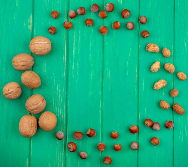 Vista dall'alto di noci con nocciole e arachidi su una superficie verde