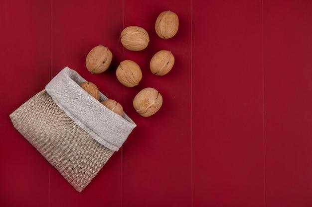 Vista dall'alto di noci in un sacchetto di tela da imballaggio su una superficie rossa