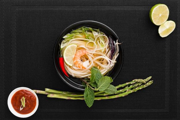 Vista dall'alto di noodles in una ciotola con asparagi