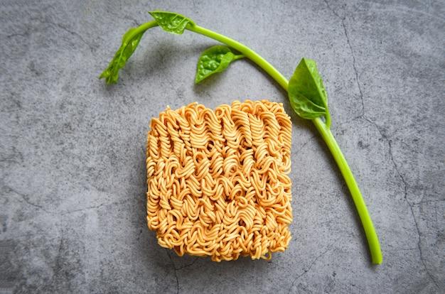 Vista dall'alto di noodles istantanei e verdure sul cibo spazzatura tailandese di tagliatella scuro o dieta malsana fast food