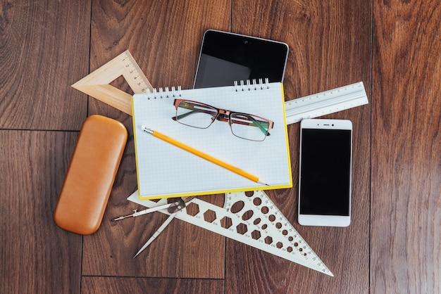 Vista dall'alto di notebook, articoli di cancelleria, strumenti di disegno e alcuni occhiali. improvvisare.